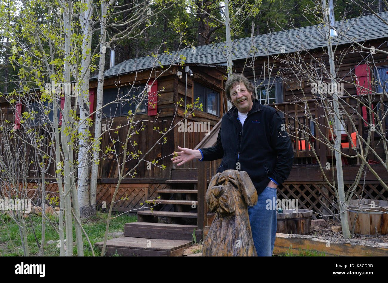 Jeff Eckstrom in front of his cabin near Nederland, CO, Dog sculpture, mountain living - Stock Image