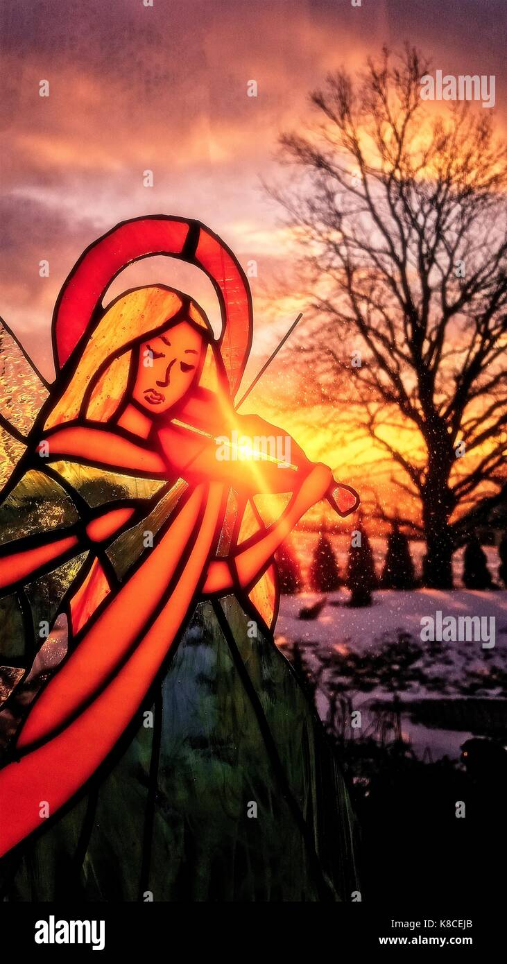 An angel playing the violin. Stained glass angel. Winter background. Colorful scenery. Sun shining through the stained Stock Photo