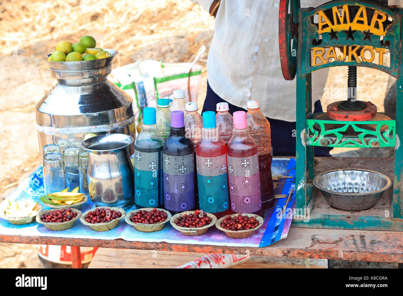 Vendor displaying raw mango cut pieces , red berries , cold drinks with a pop sickle machine on the side - Stock Image
