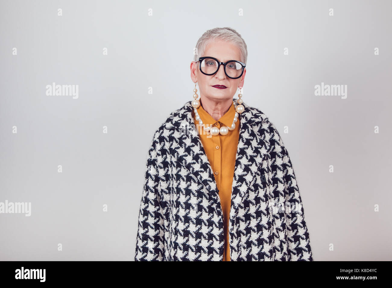8b3bb819c Stylish and elegant old woman in glasses on a white background Stock ...
