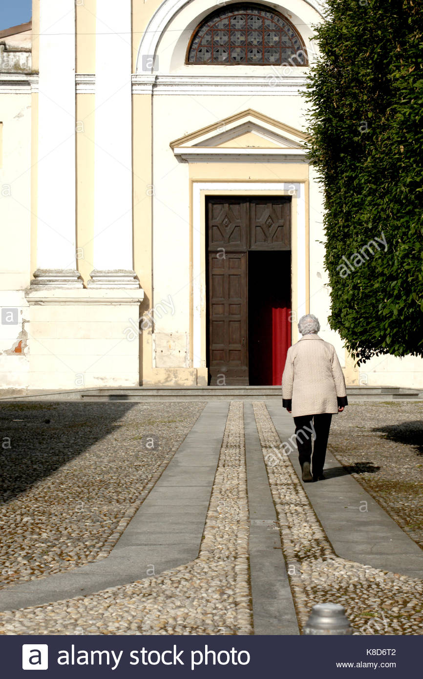 old woman entering  a church in an italian village - Stock Image