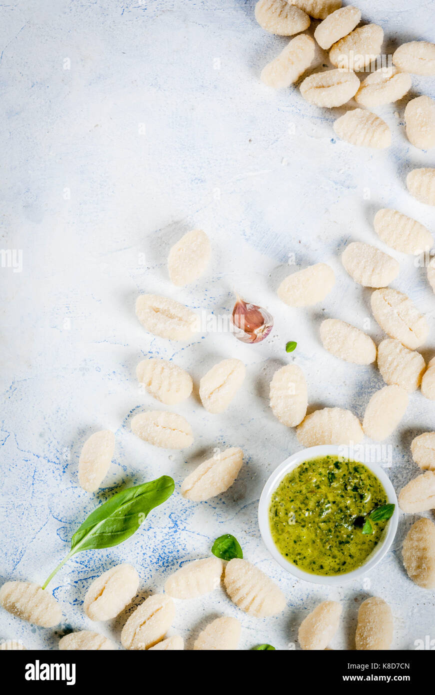 Raw uncooked homemade potato gnocchi with flour, grated parmesan cheese, basil and pesto sauce. On concrete light - Stock Image