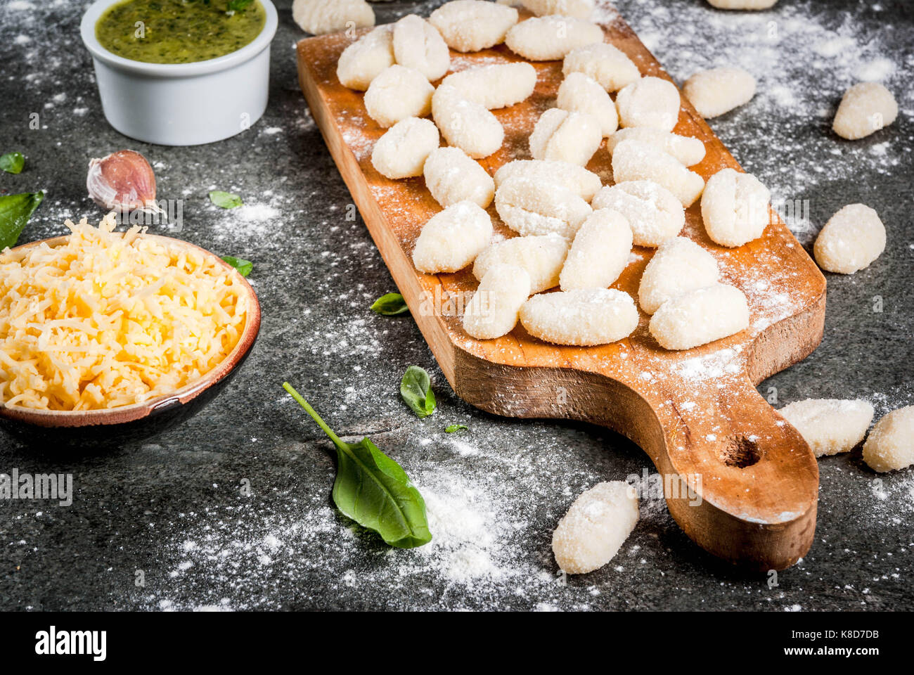 Raw uncooked homemade potato gnocchi with flour, grated parmesan cheese, basil and pesto sauce. On concrete grey - Stock Image