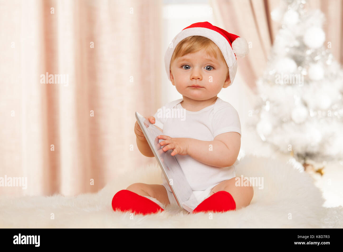 930f3bb48 Cute santa baby holds tablet Stock Photo: 160102071 - Alamy