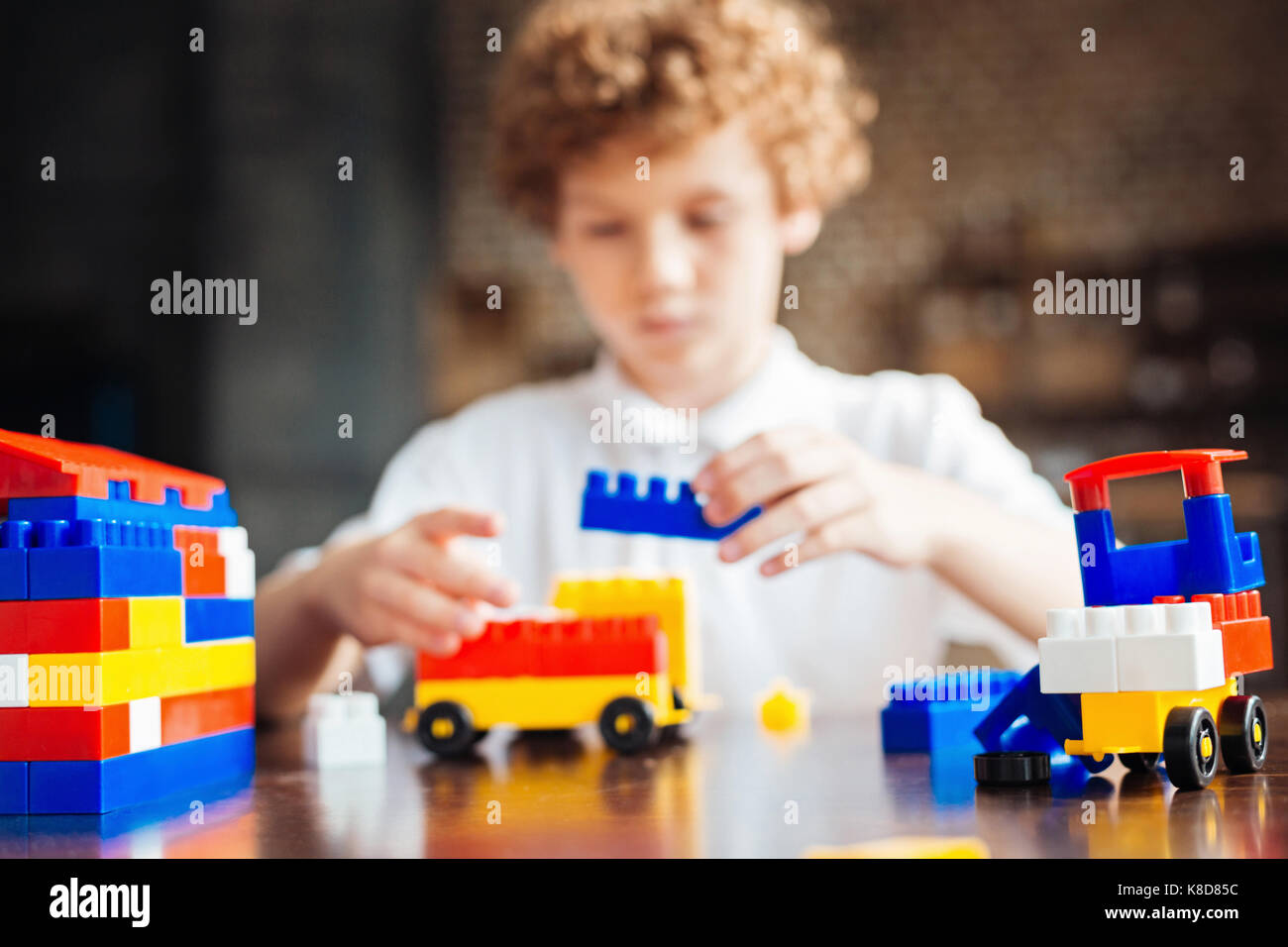 Preteen boy playing with colorful building blocks - Stock Image