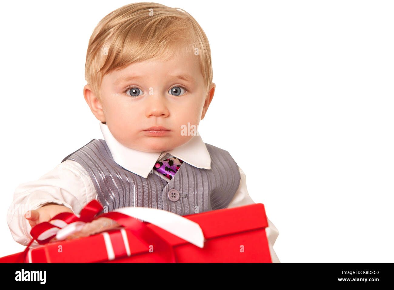Baby boy holds a big red gift box - Stock Image