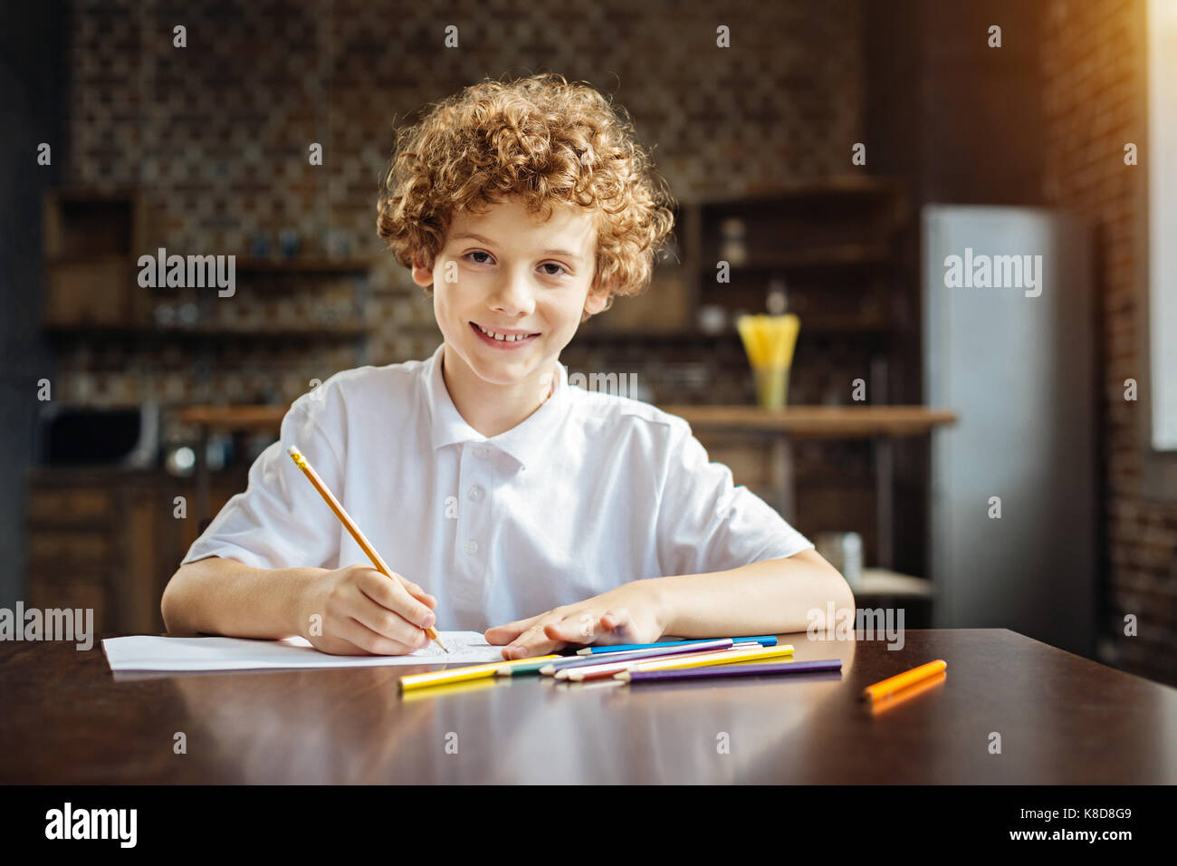 Curly haired preteen boy looking into camera while drawing - Stock Image