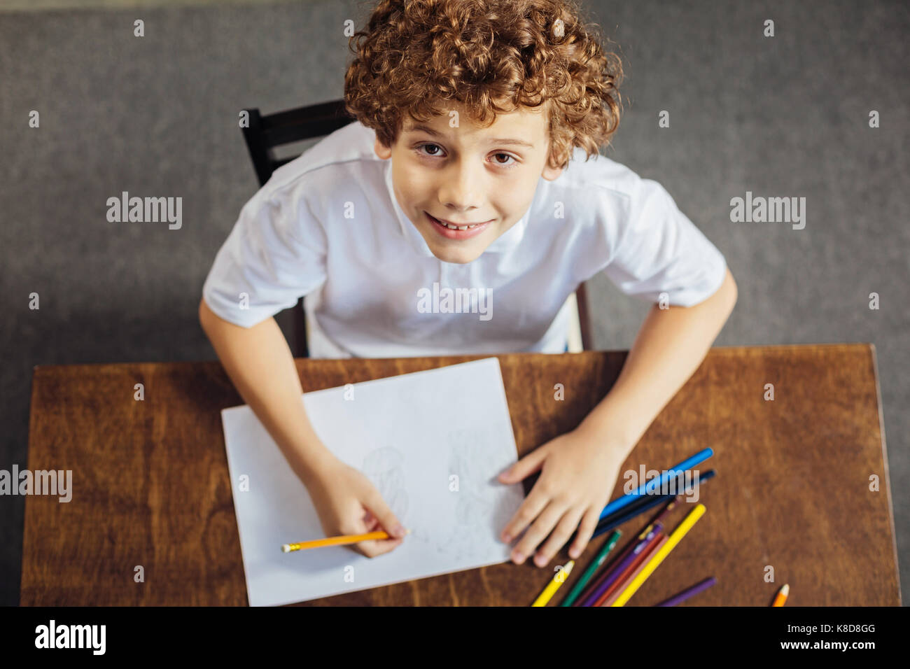Preteen boy with curls looking into camera with slight smile - Stock Image