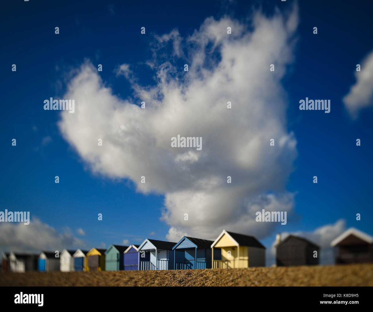 A huge white cloud against a blue sky towers over a row of colourful beach huts at Calshot Hampshire England - Stock Image
