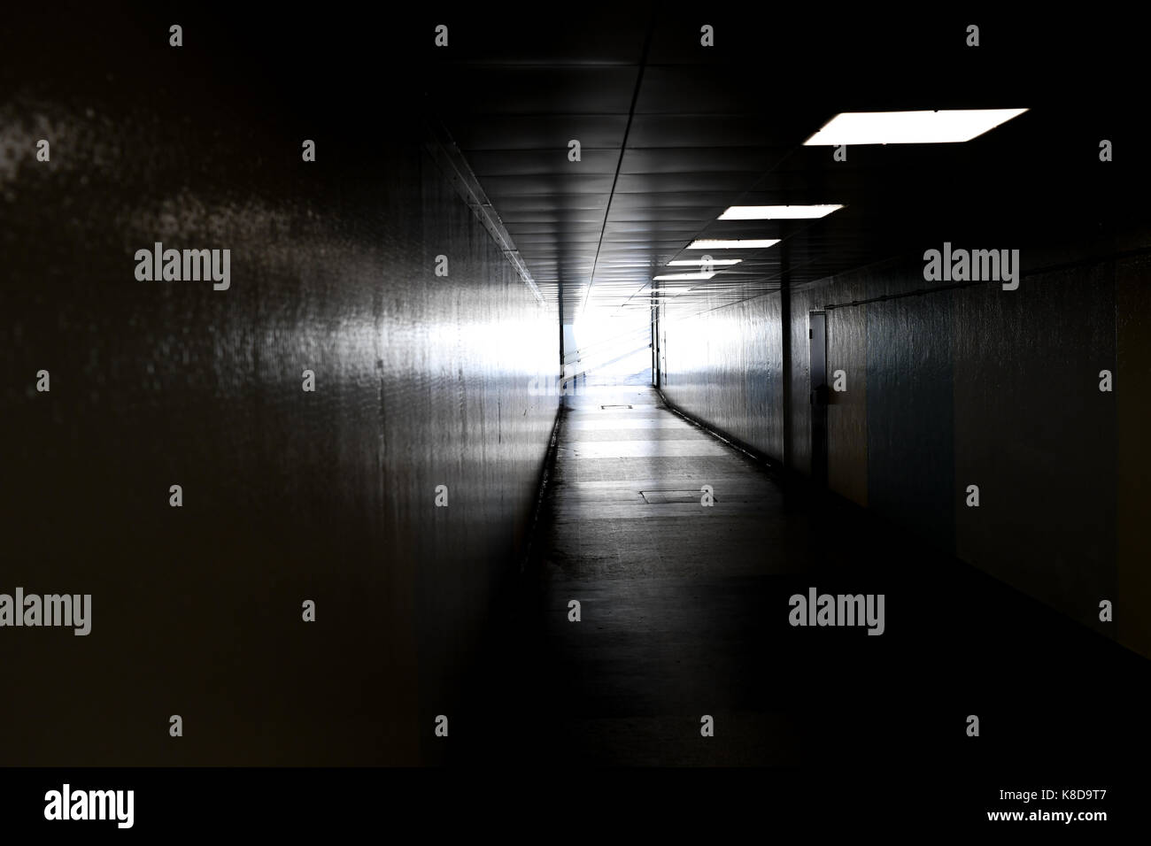 A view down into a underground dark subway leading to the exit with light bursting from it - Stock Image