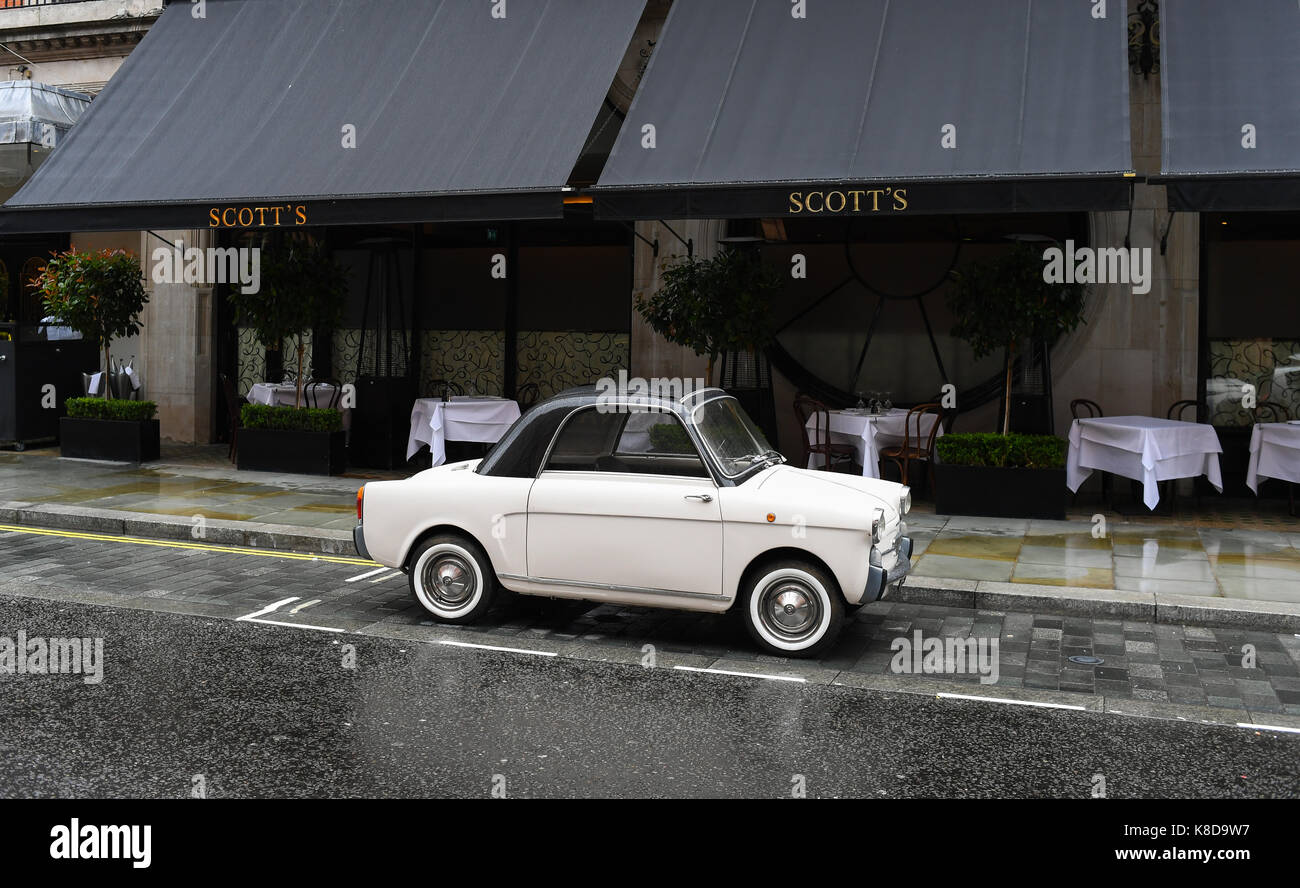 A cute small white car outside Scotts restaurant in London England - Stock Image