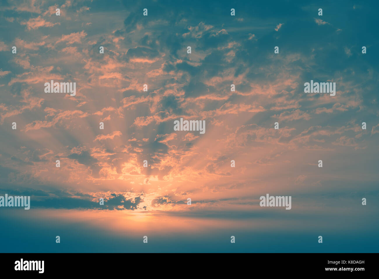 Colourful cloudy sky at sunset. Vintage style background image. - Stock Image