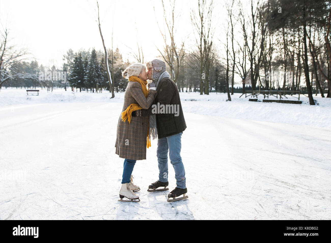 Senior couple in sunny winter nature ice skating. - Stock Image