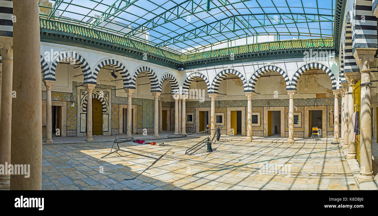 TUNIS, TUNISIA - SEPTEMBER 2, 2015: The covered courtyard of Bir Lahjar Madrasa with preserved arcades and tile - Stock Image