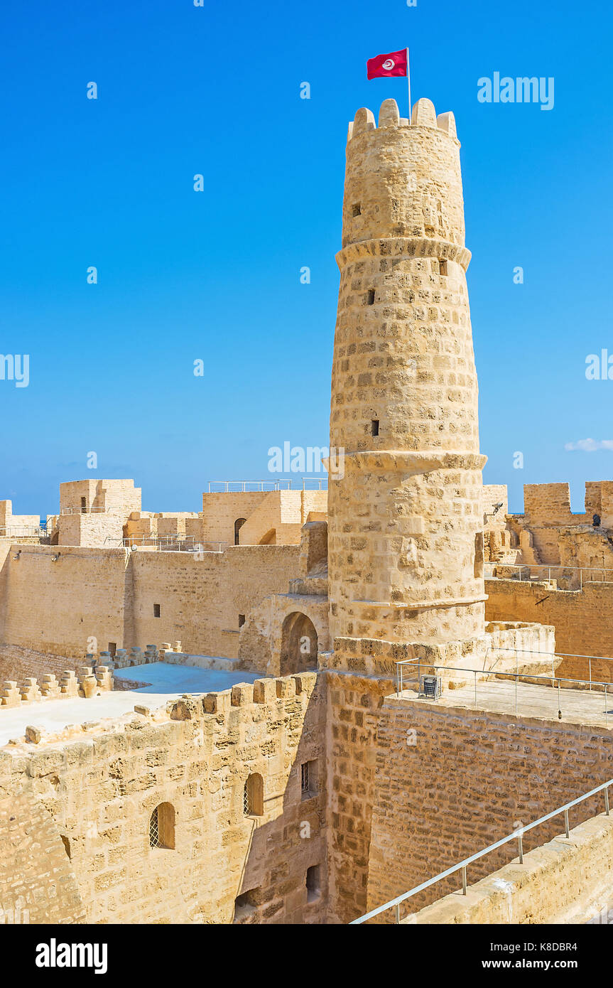 The yellow stone fortress of Ribat with tall tower, walls with battlements and many interesting structures to discover, Stock Photo