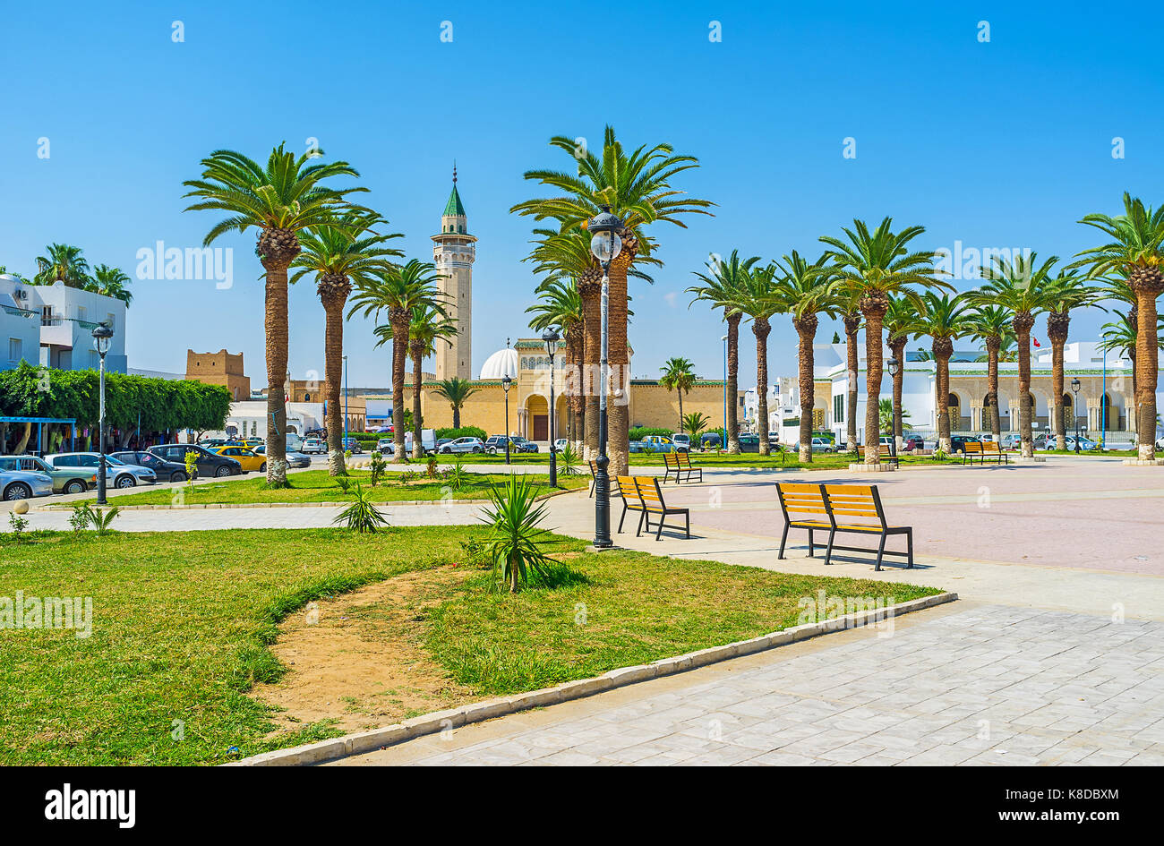 The scenic park with palms in front of Ribat fortress, the mosque of Habib Bourguiba is seen behind the trees, Monastir, - Stock Image