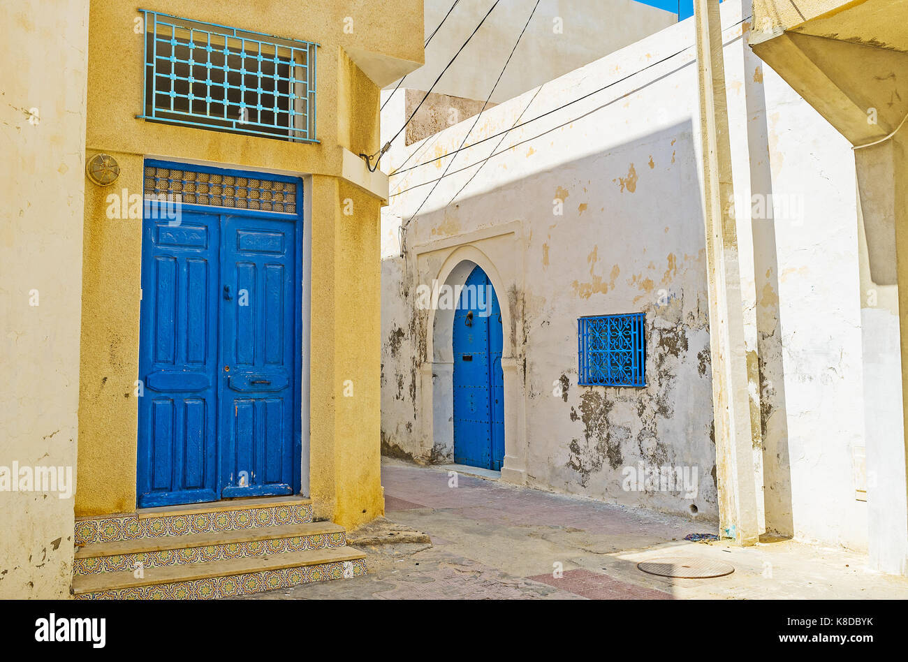 The quiet street of Medina with historic edifices, traditional blue doors and tiled stairs, Monastir, Tunisia. - Stock Image