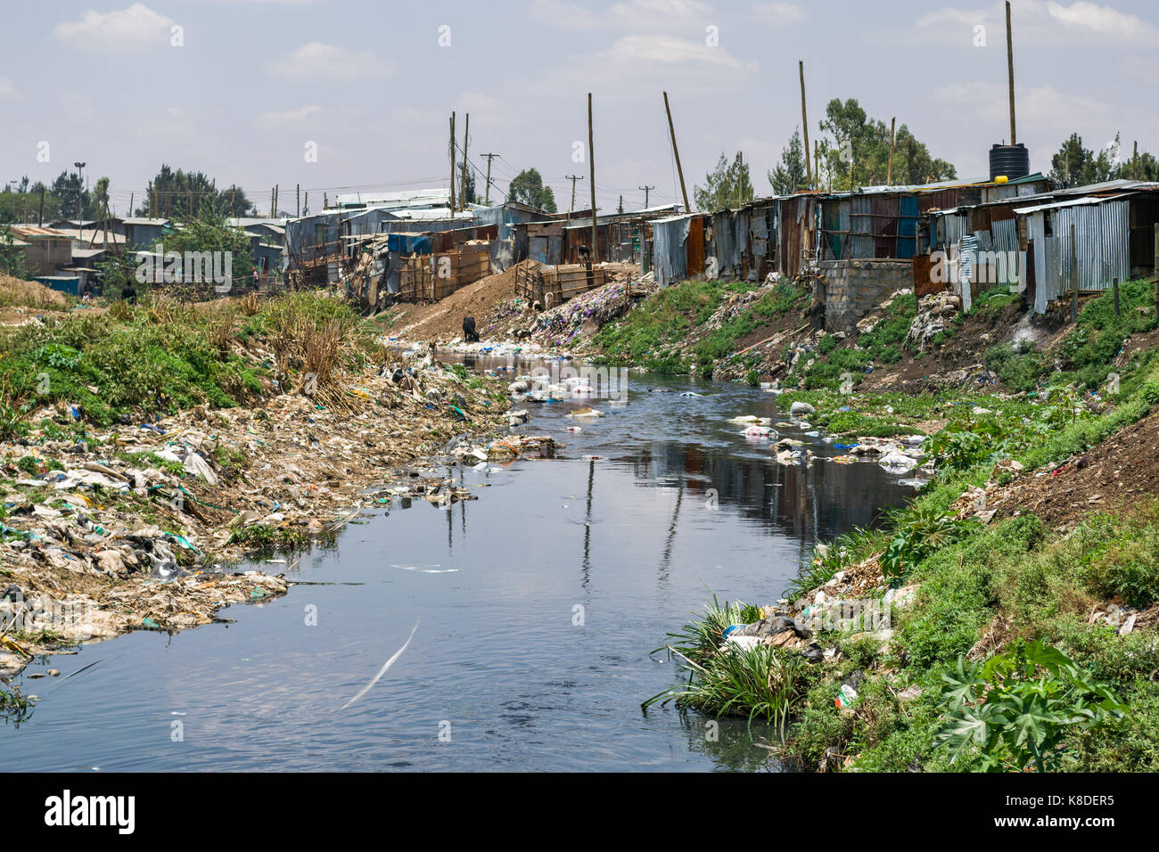 Slum shacks and buildings line the Ngong river which is polluted with rubbish, plastic waste and garbage, Nairobi, - Stock Image