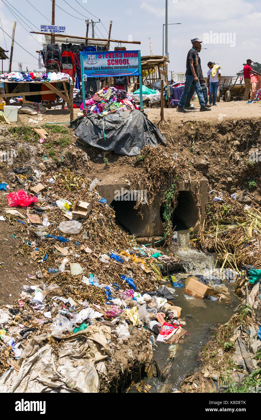Drainage waste pipes empty water into the Ngong river which is polluted with rubbish, plastic waste and garbage, - Stock Image