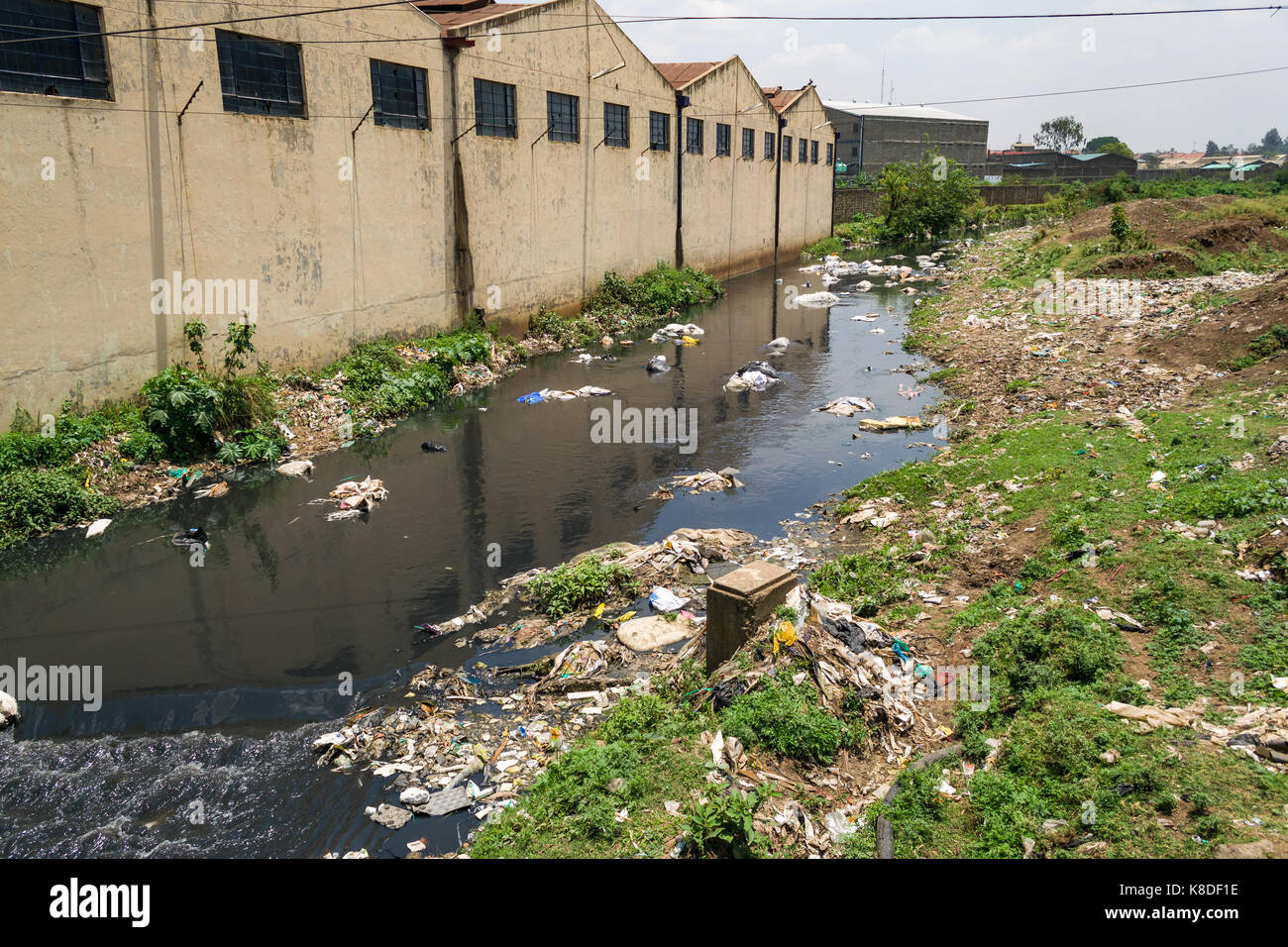 Factory buildings line the Ngong river which is polluted with rubbish, plastic waste and garbage, Nairobi, Kenya - Stock Image