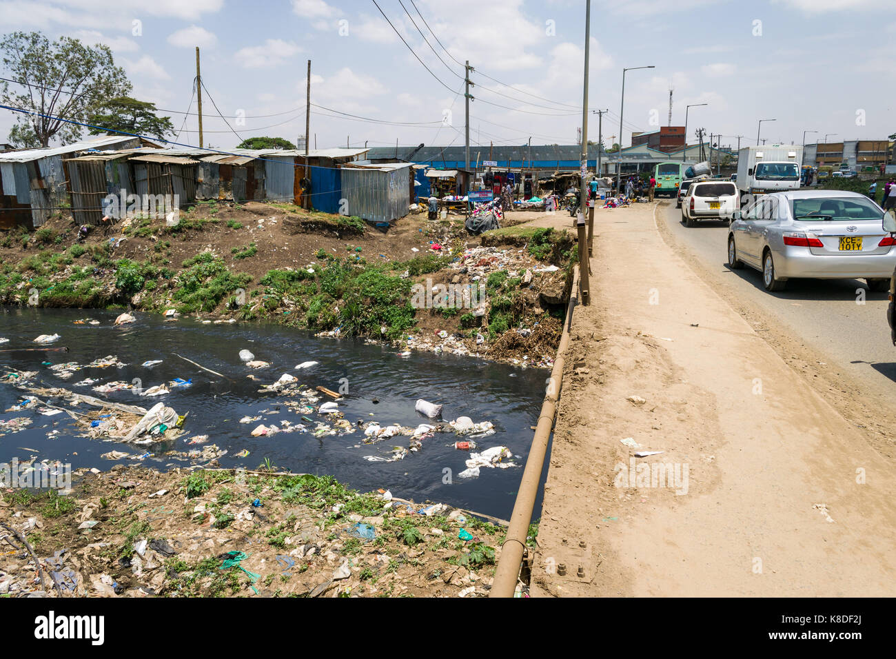 Enterprise road bridge crosses the Ngong river which is polluted with rubbish, plastic waste and garbage, slum shacks - Stock Image