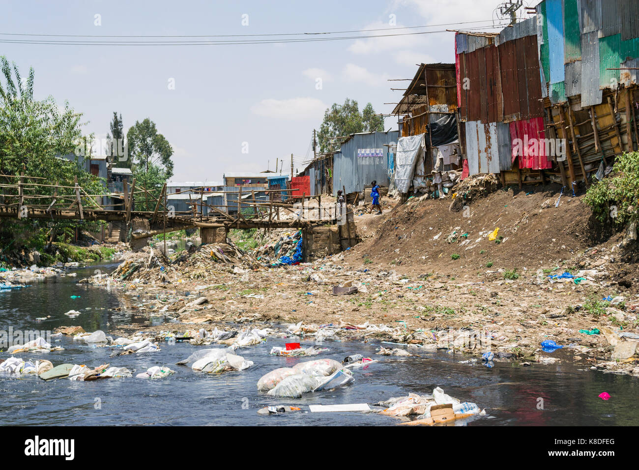 Slum shacks line the Ngong river which is polluted with rubbish, plastic waste and garbage, a makeshift wooden bridge - Stock Image