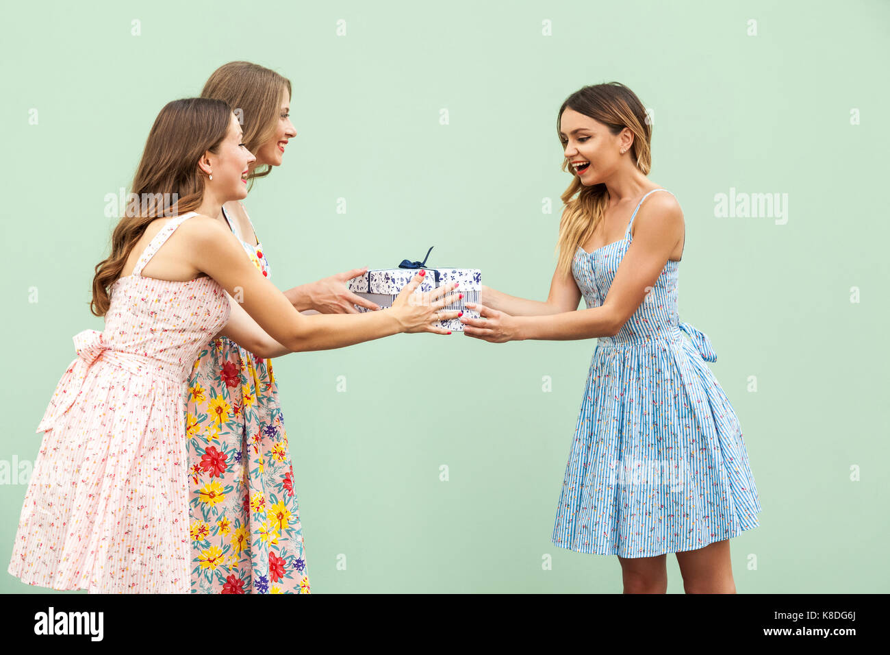 Young Adult Cute Girl Giving Surprise Gift To Hes Pretty Friend Concept Of Birthday And Party Isolated On Green Background