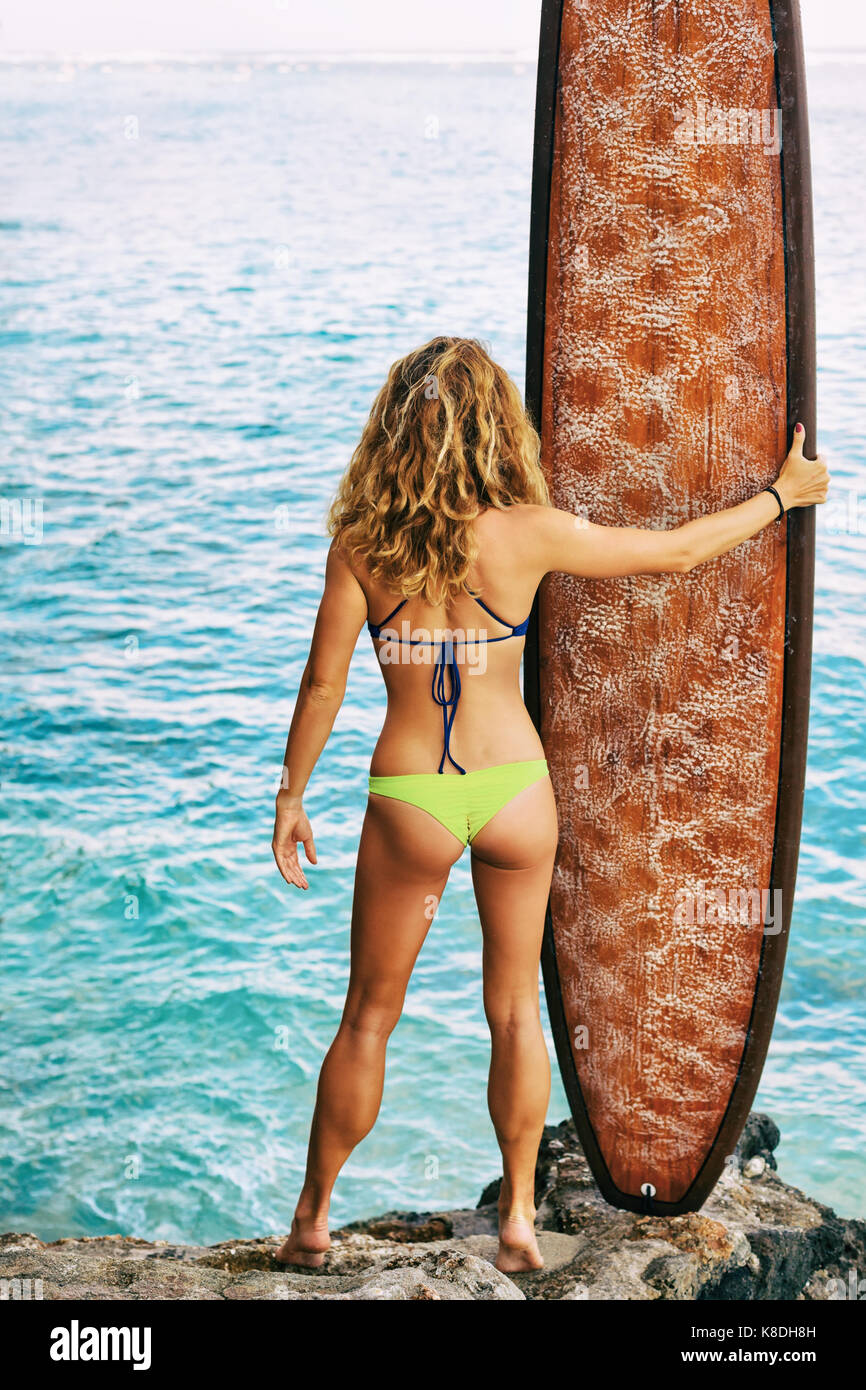 Beautiful surfer girl in bikini holding surf board stand on beach high cliff and look at ocean. Back view. People Stock Photo