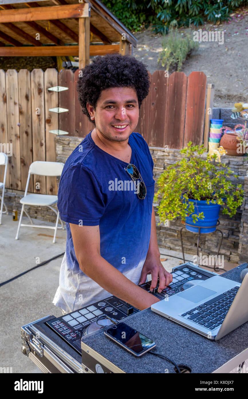 Hispanic man, disc jockey, deejay, dj, playing music, musical entertainment, pool party, Castro Valley, Alameda - Stock Image