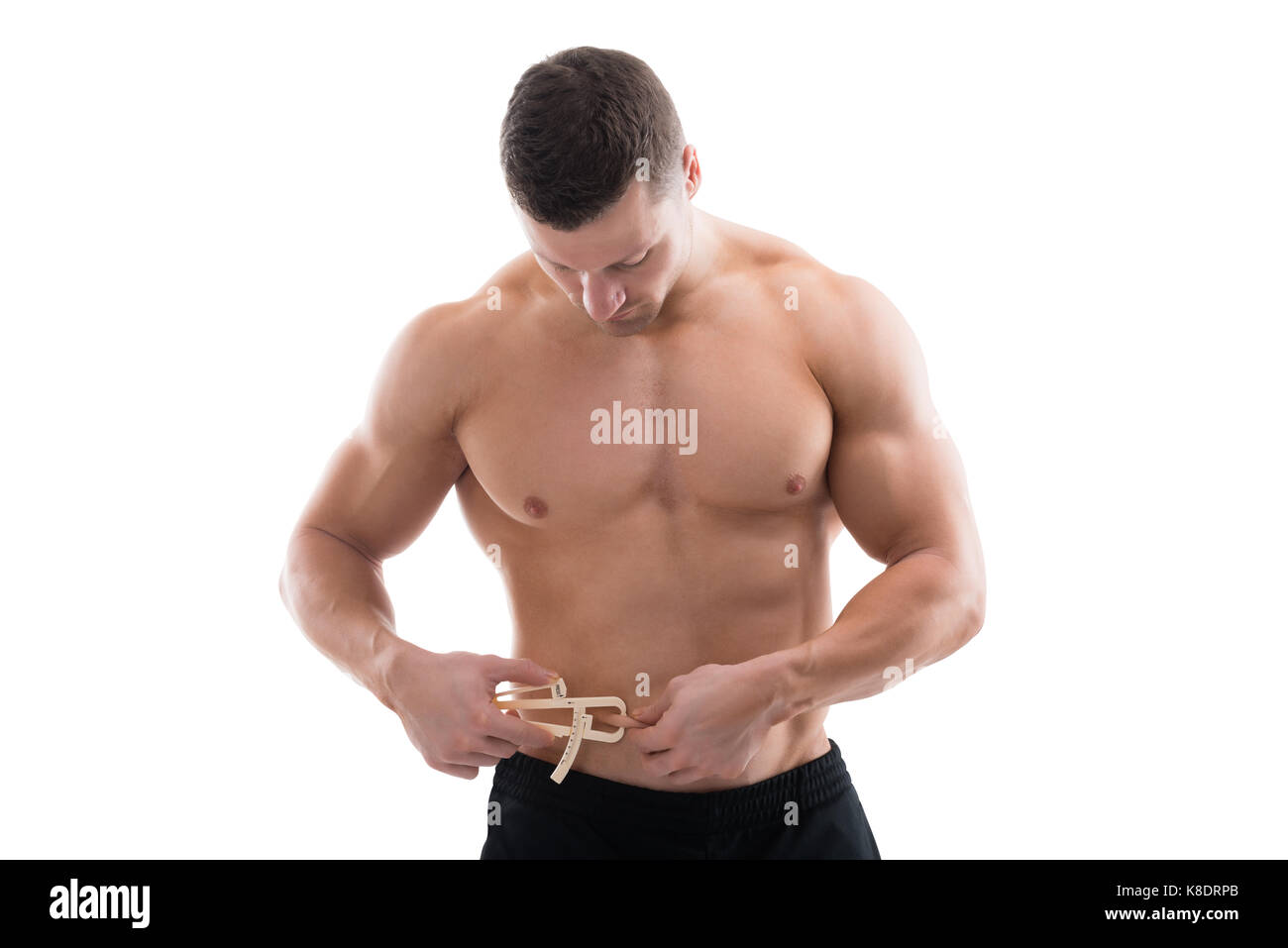 Mid adult muscular man measuring fats with caliper against white background - Stock Image
