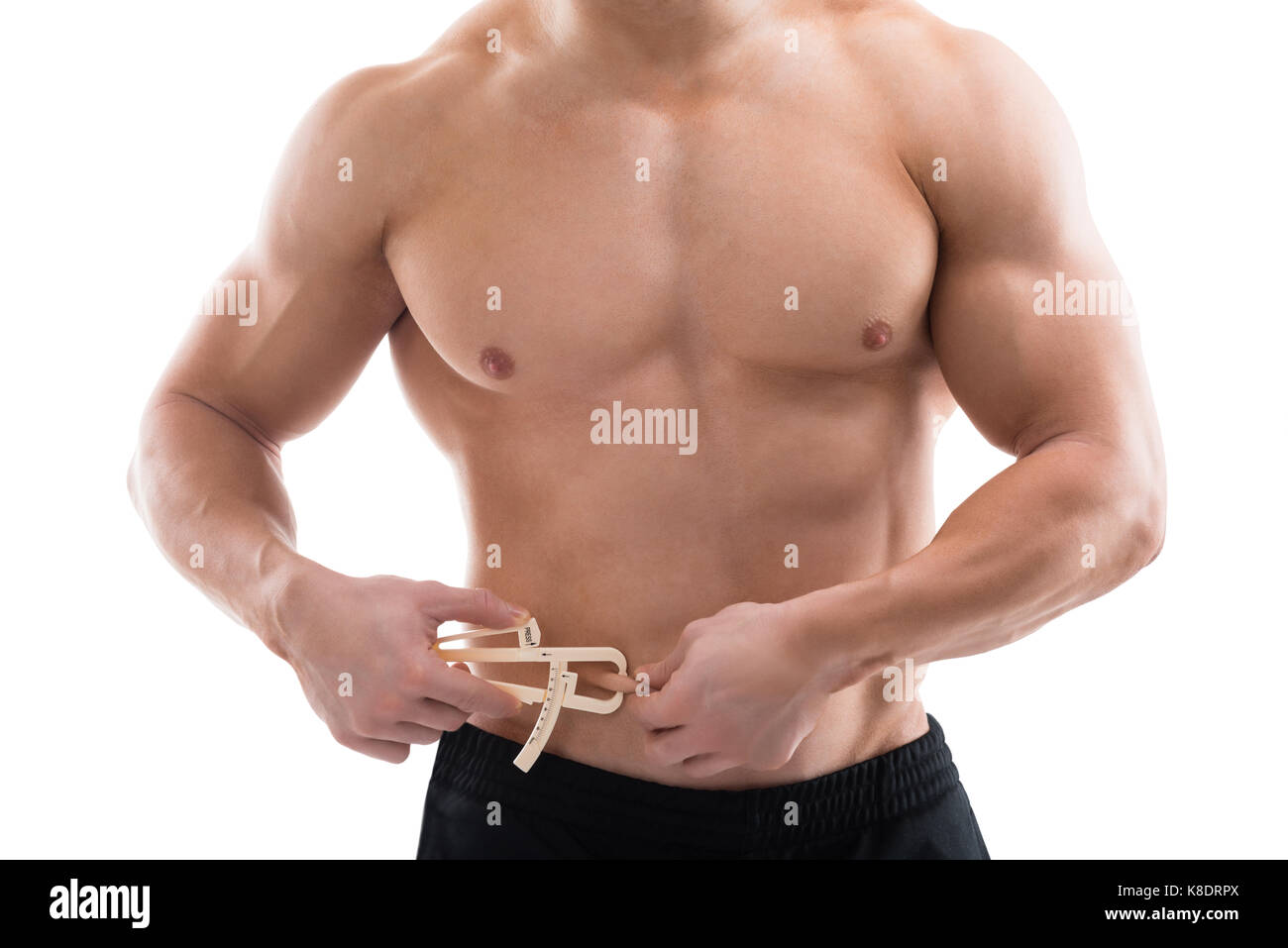 Midsection of strong man measuring fats with caliper against white background - Stock Image