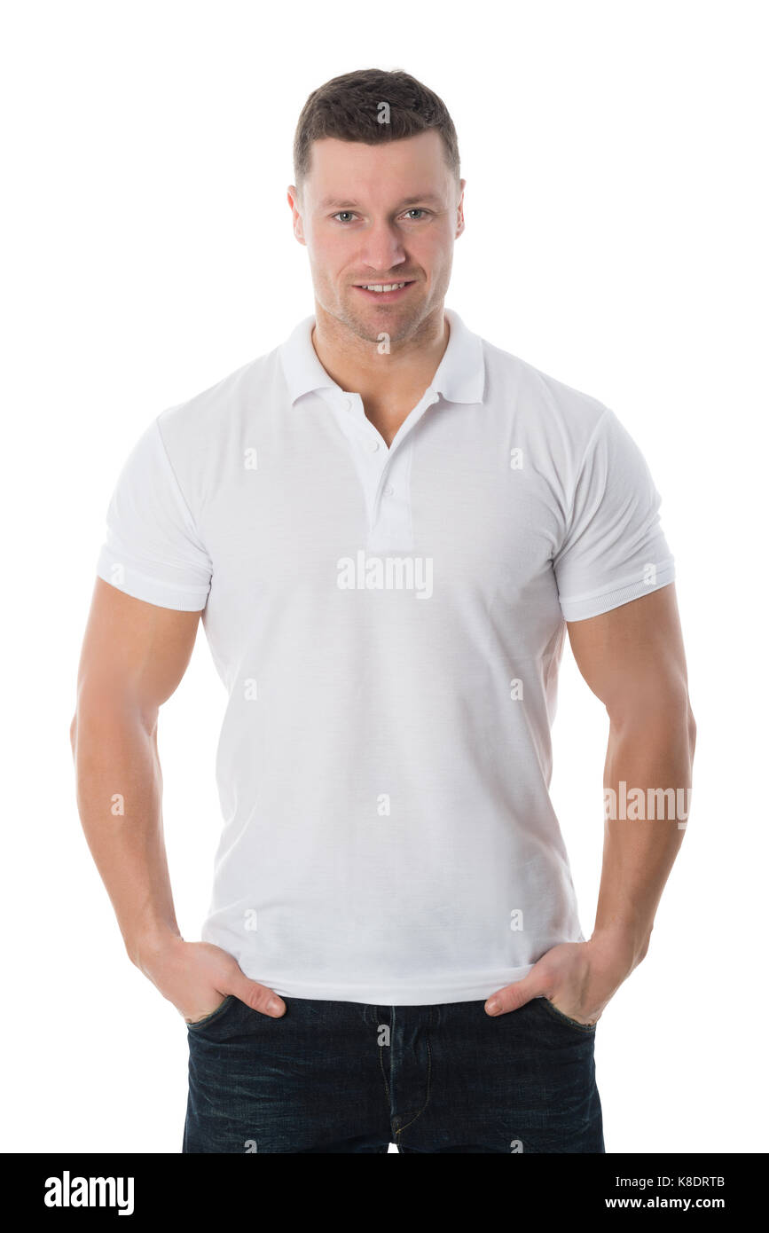 Portrait of smiling man in casuals standing with hands in pockets against white background Stock Photo