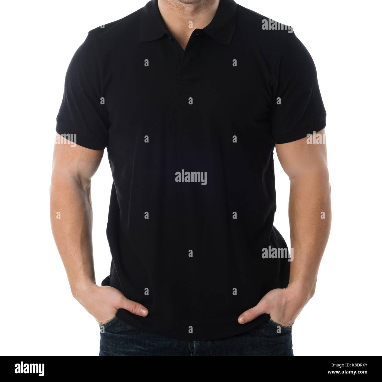 Midsection of man wearing blank black tshirt standing with hands in pockets against white background - Stock Image