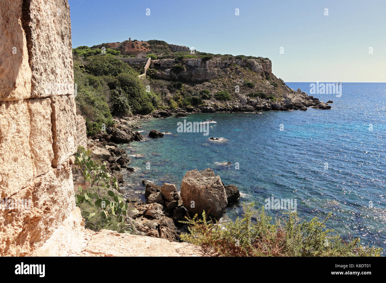 Coastal view on Balearic island of Minorca in the Mediterranean sea with anchored boats in a cove - Stock Image