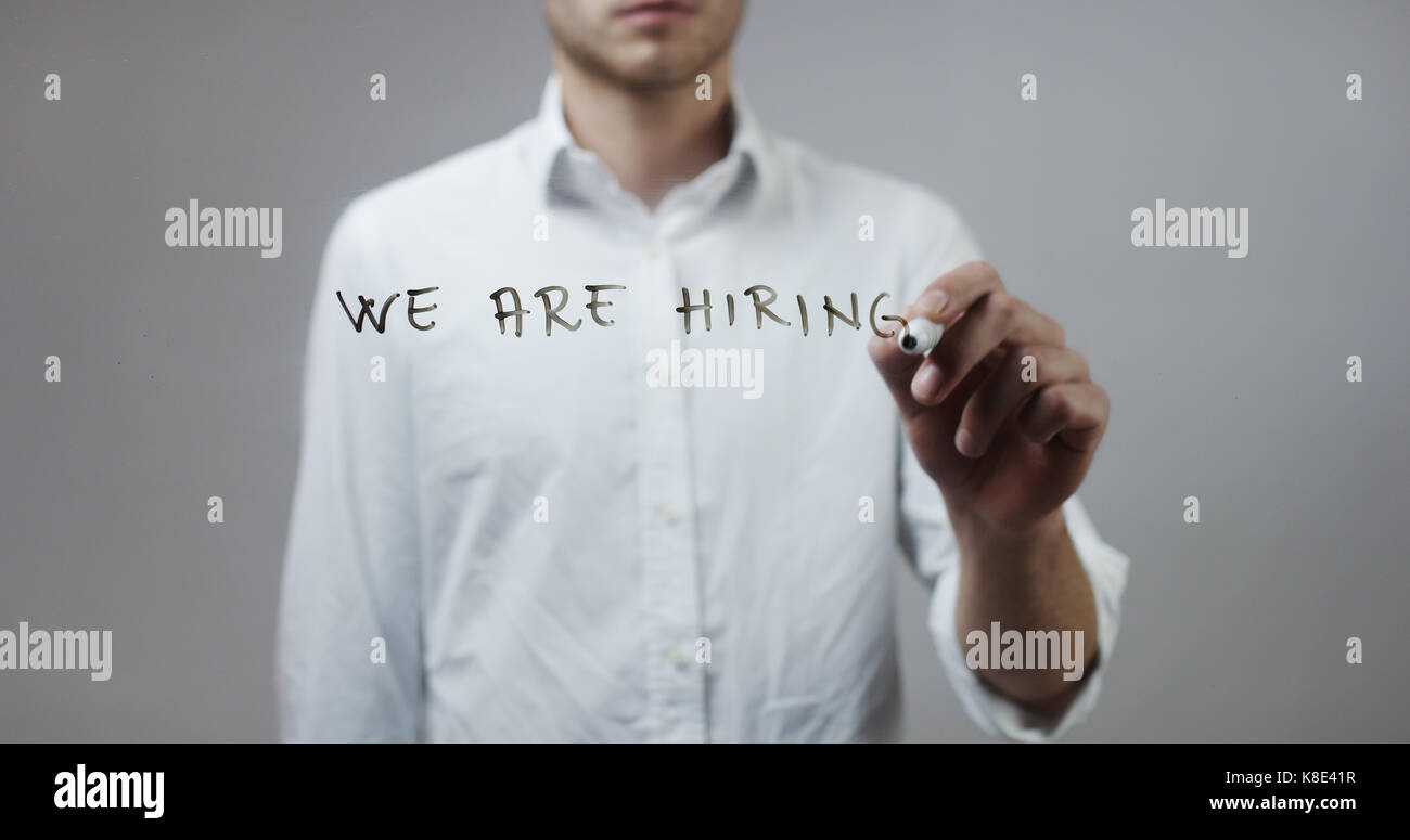 We are hiring , Man Writing on Glass - Stock Image
