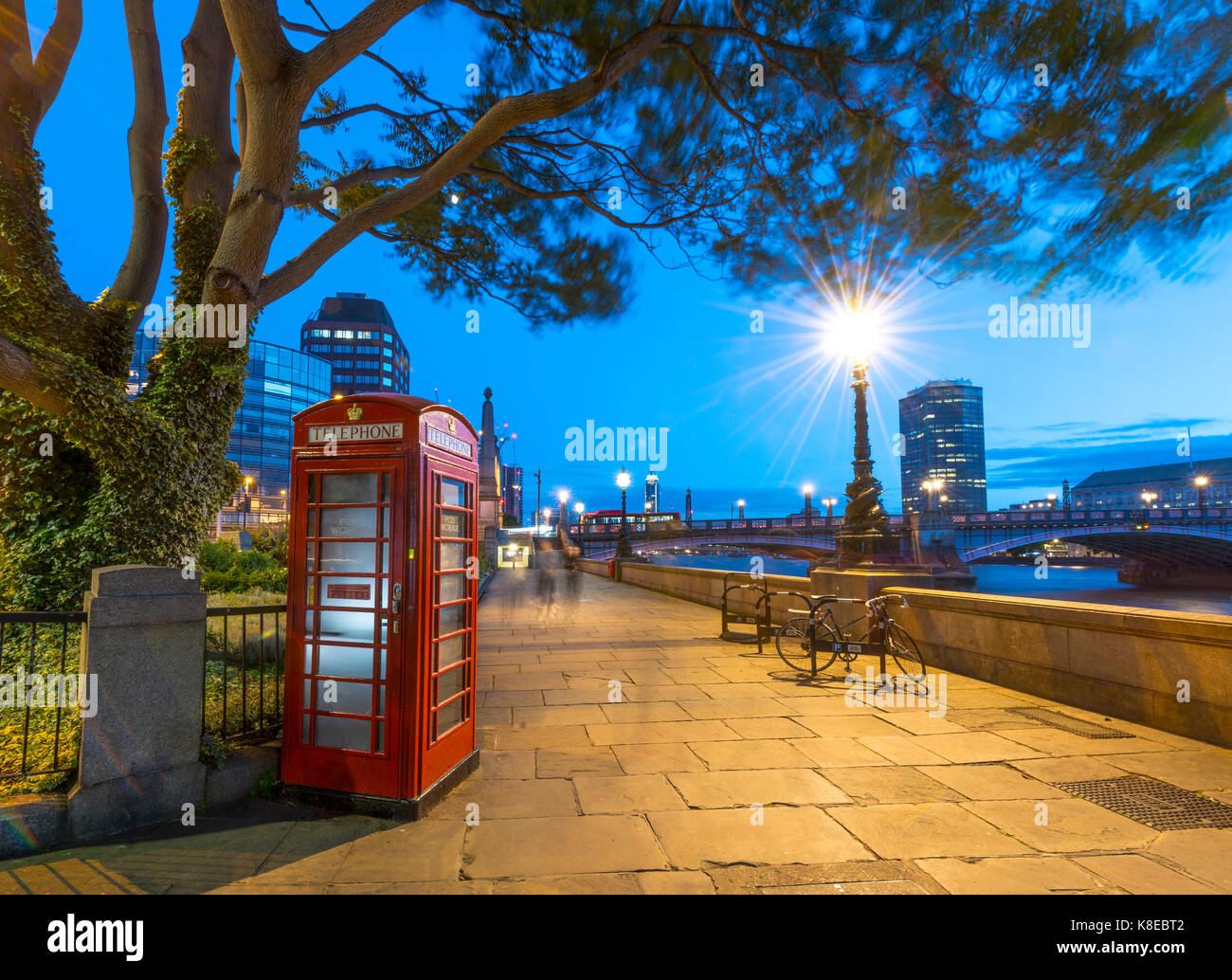 Typical red telephone box, pedestrian walkway next to the Thames, London, England, Great Britain - Stock Image