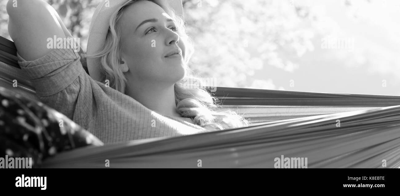 Woman Relaxing In Hammock - Stock Image