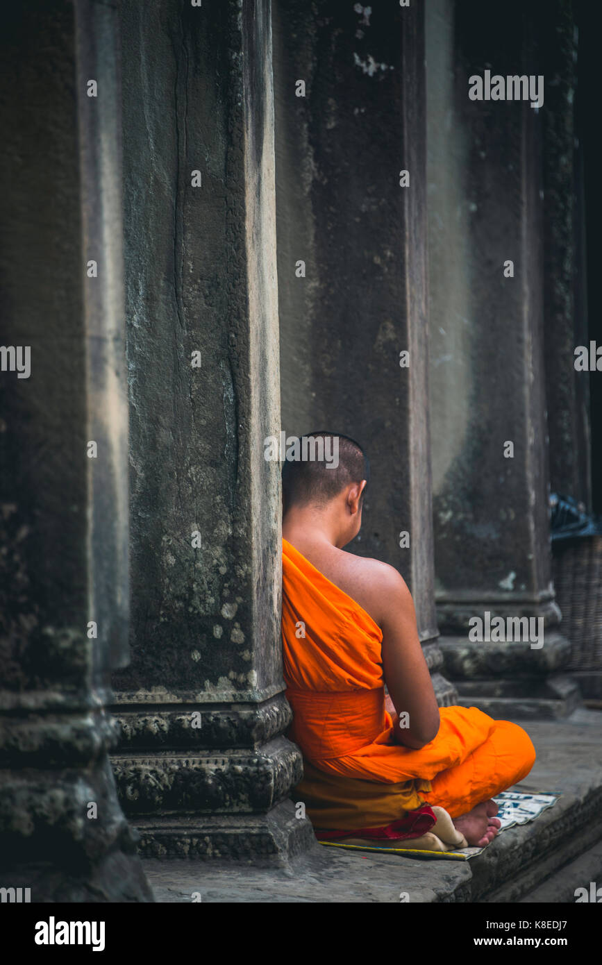 Buddhist monk meditates in colonnade, temple complex of Angkor Wat, Angkor Archaeological Park, province of Siem Stock Photo