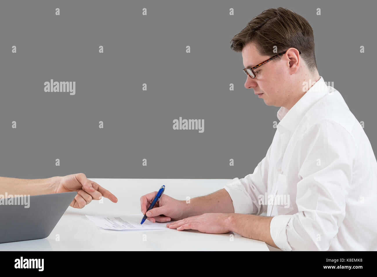 Closeup of male hand pointing where to sign a contract, legal papers or application form. - Stock Image