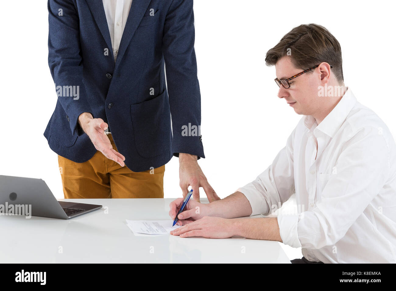 Two young businessmen signing contracts at office desk - Stock Image