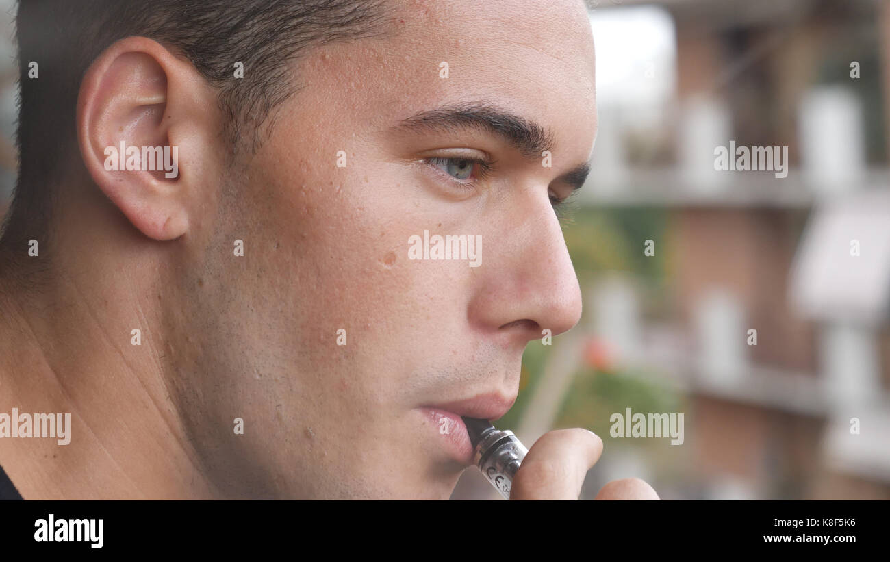 Man smoking ecig on balcony - Stock Image