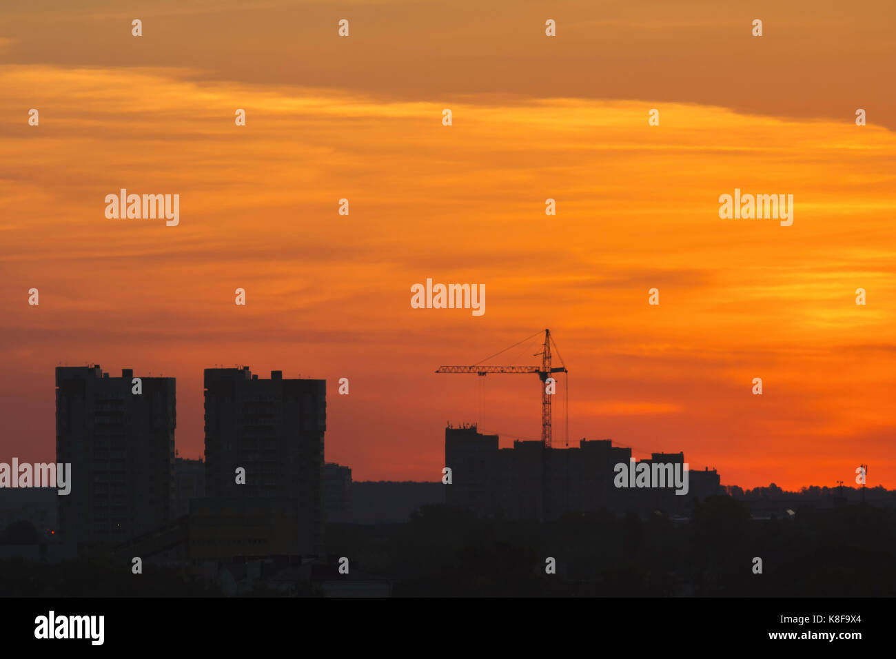 Construction cranes near residential apartments - view on sunrise, horizontal - Stock Image