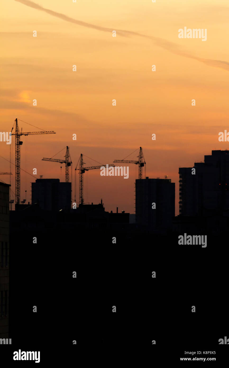 Construction cranes near residential apartments - view on sunrise, vertical - Stock Image
