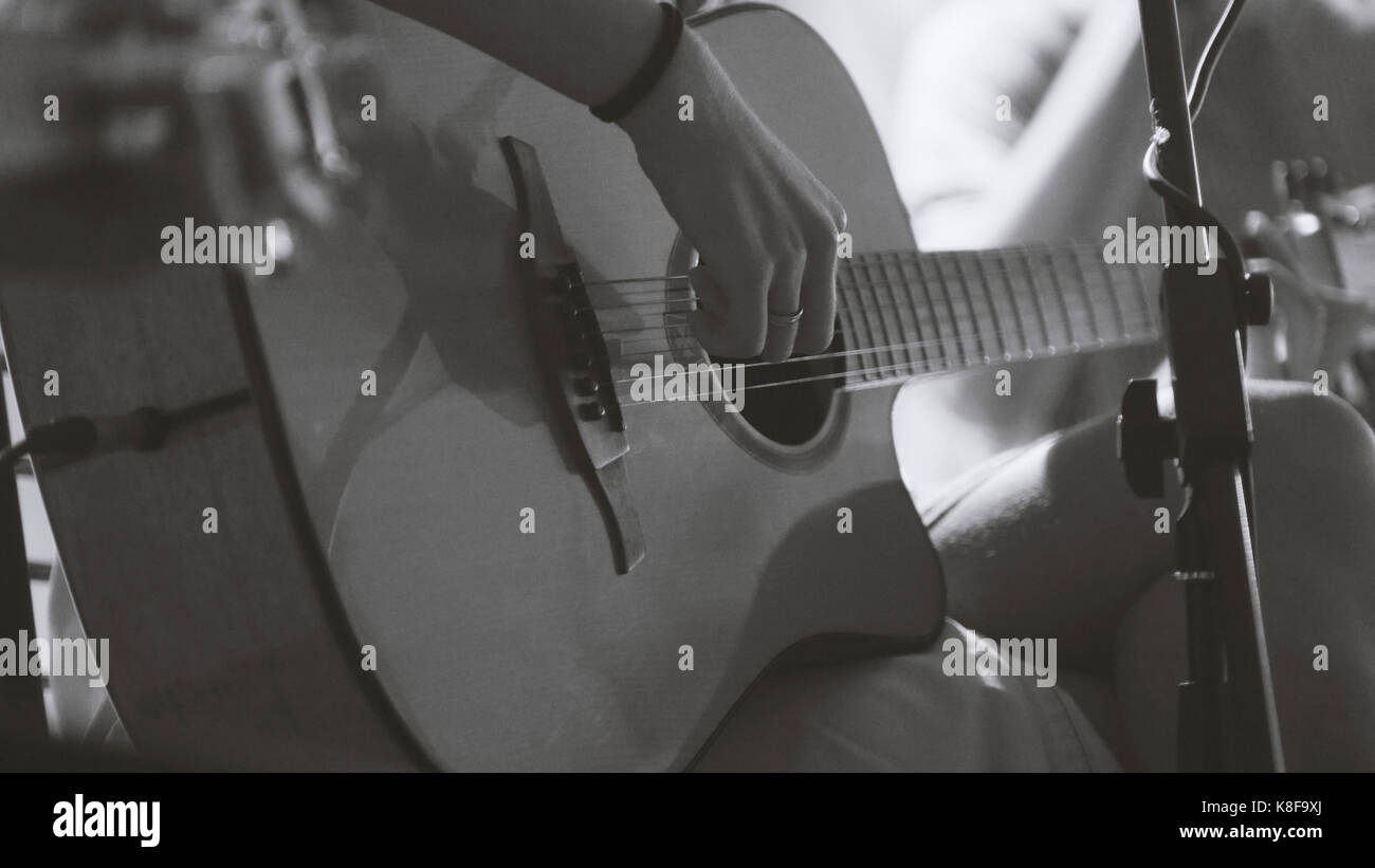 Musician in night club - guitarist plays blues acoustic guitar, extremely close up - black and white - Stock Image
