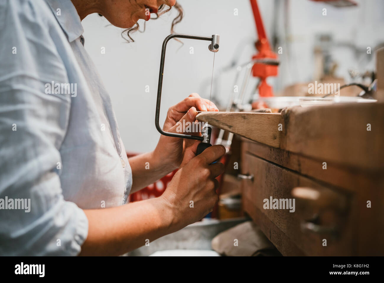 Cropped view of female jeweller using coping saw at workbench - Stock Image