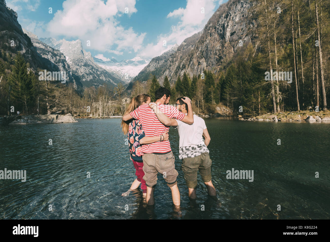 Rear view of three young adult friends ankle deep in mountain lake, Lombardy, Italy - Stock Image