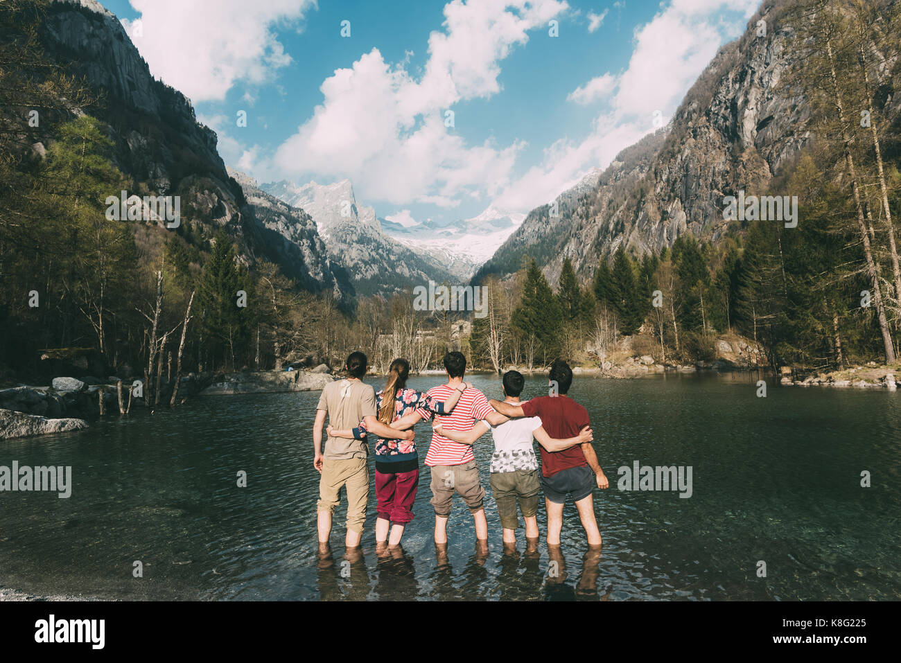 Rear view of five adult friends ankle deep in mountain lake, Lombardy, Italy - Stock Image