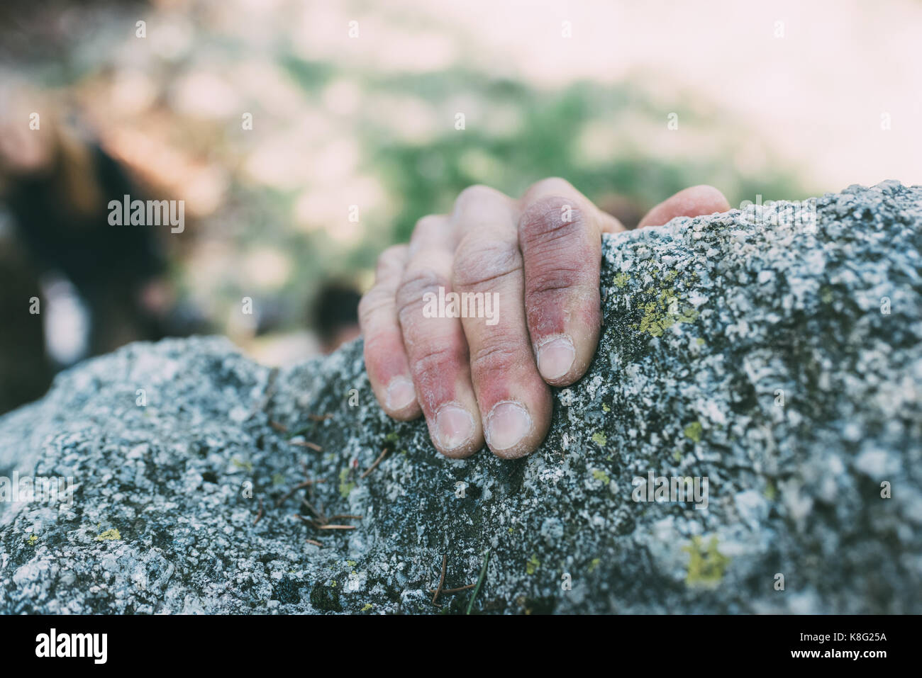 Hand of male boulderer gripping boulder edge, Lombardy, Italy - Stock Image