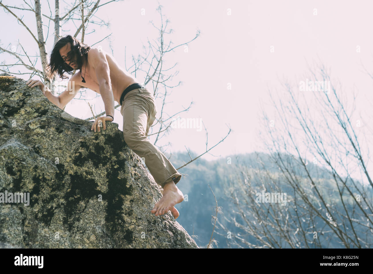 Bare chested and bare foot male boulderer climbing boulder, Lombardy, Italy - Stock Image