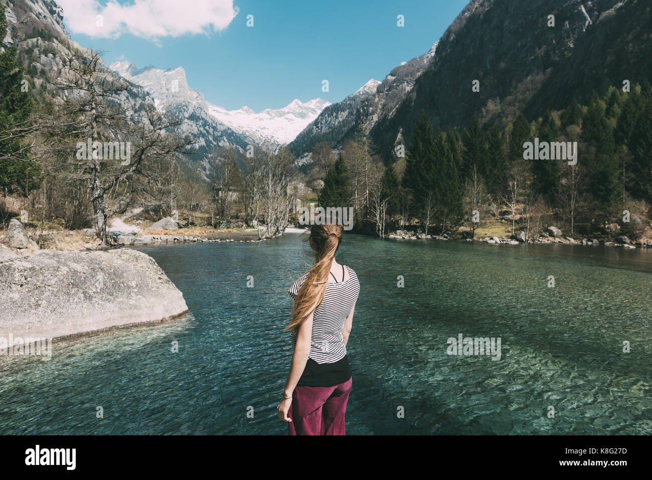 Rear view of young woman looking out over lake, Lombardy, Italy - Stock Image